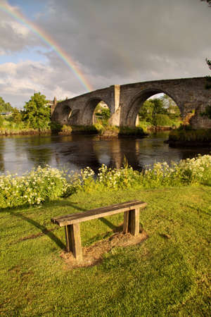The ancient medieval bridge at Stirling captured in the soft light of early morning with a rainbow in the background. photo