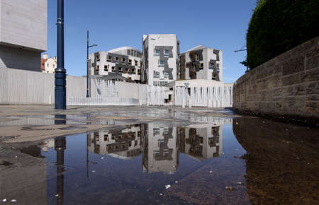 Rear view of the Scottish parliament in Edinburgh reflected in a pool of rainwater following a typical Scottish midsummer downpour.