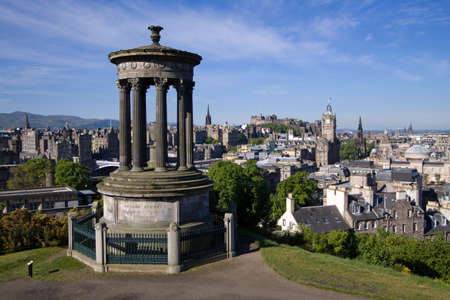 Edinburgh City and Castle viewed from Calton Hill on a beautiful summer morning with the Dugald Stewart monument in the foreground.