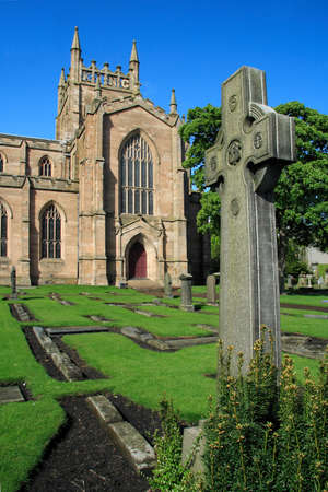 robert bruce: Dunfermline Abbey with an ornate sculptured Celtic cross in the foreground. For centuries Dunfermline was the Scottish capital and its Abbey one of the most powerful in Scotland. Robert the Bruce is entombed here. Stock Photo