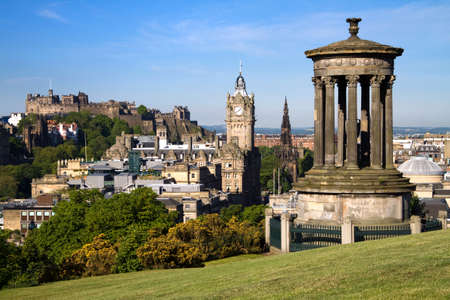 scots: Edinburgh summer city view captured from Calton Hill with the Dugald Stewart monument in the foreground and the castle, Scott monument and Balmoral clock tower in the background.