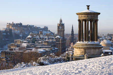 scots: Edinburgh winter city view captured from Calton Hill with the Dugald Stewart monument in the foreground and the castle, Scott monument and Balmoral clock tower in the background. Stock Photo