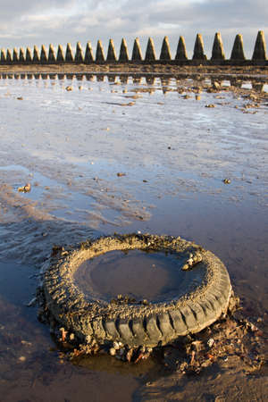 Discarded tyre on beach suggesting environmental pollution. The structure in the background is Cramond Causeway near Edinburgh. Stock Photo - 9555439