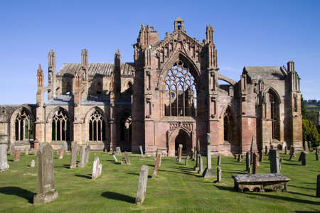 Melrose Abbey in the Scottish Borders is a beautiful and atmospheric red sandstone medieval ruin. It is also renowned as the poignant setting in which the embalmed heart of King Robert the Bruce was laid to rest. Stock Photo - 9555440