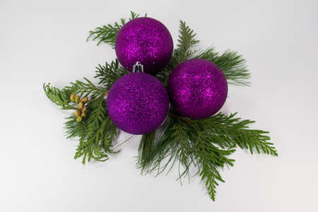 Three purple Christmas ornaments on a bed of evergreens