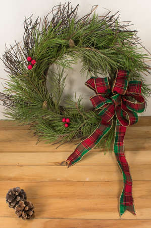 A beautiful handmade bow of red, green, and gold trimmed ribbon on a twig wreath with white pine boughs. pine cones, and red berries along with two pine cones sitting on a wooden floor