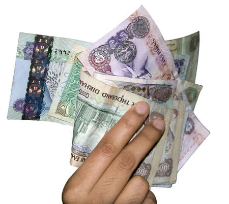 Different denomination of UAE money, held by a women