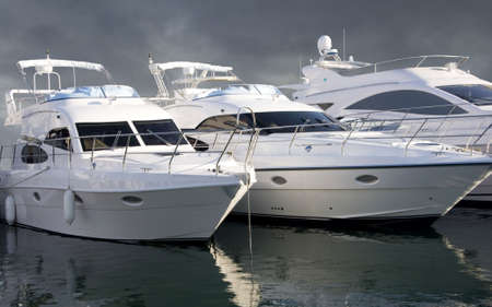 Three Yachts parked one after the other in the Dubai International Boat Show. All three yachts are Azimut. The image is with path Stock Photo