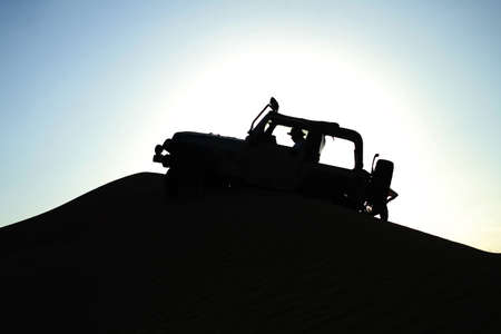 A silhouette effect of a man crusing his car in the desert sand dunes.