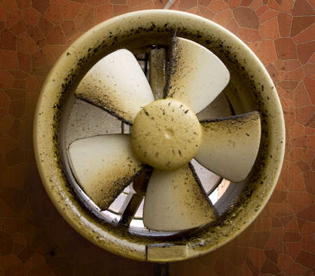 Dirty oil stained kitchen exhaust fan on a mosaic wall.