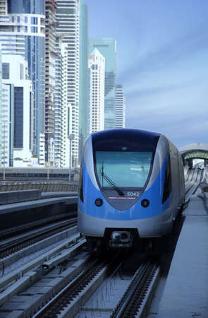 Dubai metro train arriving at the station. The image has burj al arab as background.