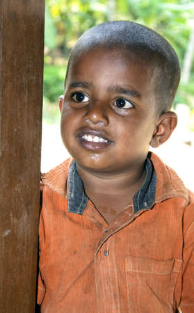 A poor young kid from India, who is dirty with running nose.