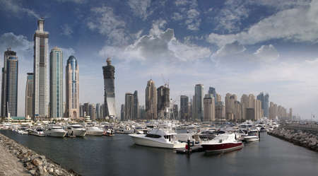 Berthing space in Dubai Marina, with several boat and yachts parked in front of the famous Marina disctrict in Dubai, UAE.