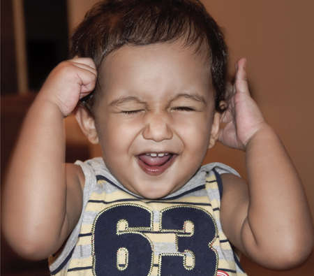 Young Indian origin infant with his happy expression, and winking his eyes