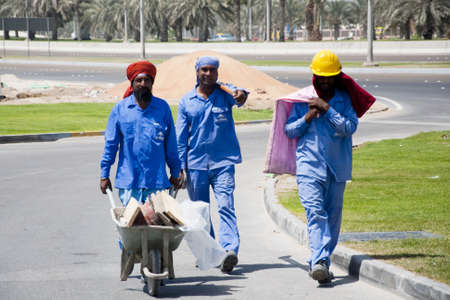 DUBAI, UAE - FEBRUARY 12: A group of construction workers in dubai, the original people behind the beuatifican of Dubai. A general image of a group of workers in their working mood in a contruction site in Dubai on 12th feb 2012.
