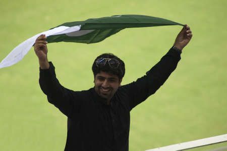 Dubai, United Arab Emirates - Nov 11: An Pakistani fan, supports his team with Pakistan National Flag during the 1st ODI cricket match between Pakistan and Sri Lanka on  Nov 11, 2011 at Dubai Sports City, Dubai, UAE.