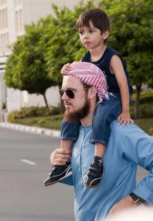 DUBAI - UAE - APRIL 06 2012: A Imam of Dubai Mosque with his son aged 3 during the March For Peace event organized by Dubai Islamic Department and Govt. of Dubai on April 06 2012 in Zabeel, Dubai.