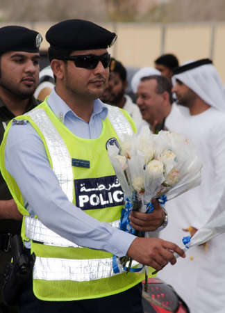 DUBAI - UAE - APRIL 06 2012: Member of Dubai Police distributing roses during the March For Peace event organized by Dubai Islamic Department and Govt. of Dubai on April 06 2012 in Zabeel, Dubai. Editorial