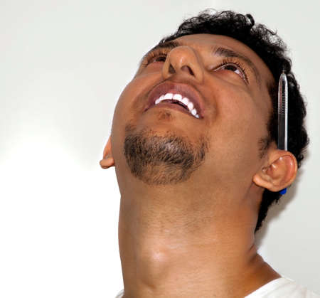 An young Indian man looking up with pen in ear