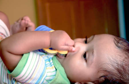 New born Indian baby biting plastic toys and sleeping in bed.