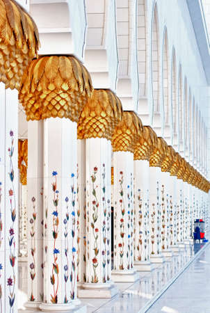 Hallway with golden decorated pillars at the entrance of the world famous Sheikh Sultan Zayed Mosque in Abu Dhabi UAE