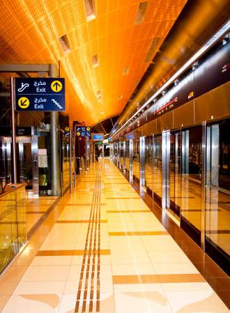 Interior of Dubai Metro Station, with signage of walk way escaltor with highlighted interior.