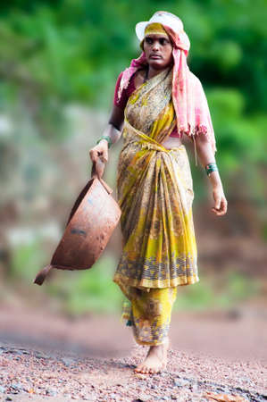 Managlore, India - June 12: A unknown Indian female construction worker carrying out her routine duty of carrying materials on head. Most of the rural constructions are done manually. Editorial
