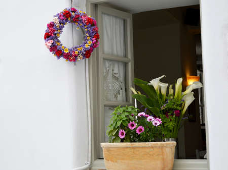 Beautiful window of Greece. Colorful flowers and leafs. Decoration Door and window wreath