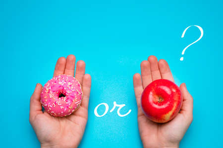 Donut and apple on the blue background. Choosing between apple and donut. Standard-Bild