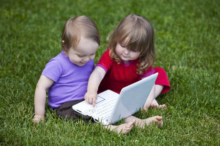 Little boy and girl using a little Laptop  The girl seems to teach Stock Photo