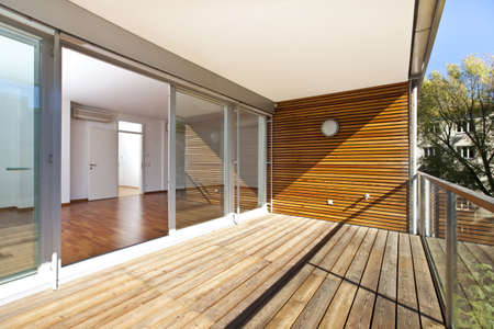 balcony: Sunlit balcony with wooden floor and wall of an architectural contemporarily apartment building in green area