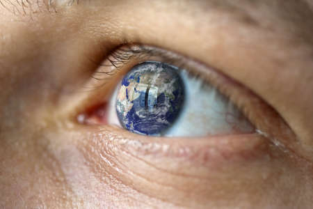 deluge: Close-Up of a male face with the earth in the eye (asia view). Symbolise Hope, fear of climate change, natural disasters like flood