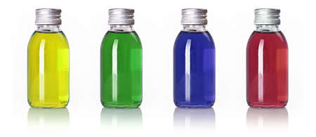 Bottles in a row with different colored liquid isolated over white background photo