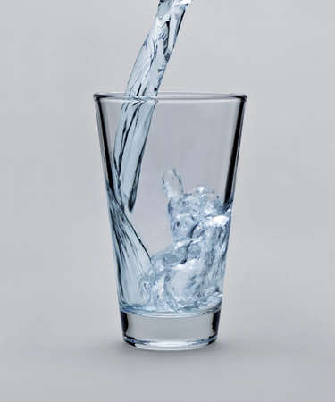 Pouring water into glass on light gray background photo