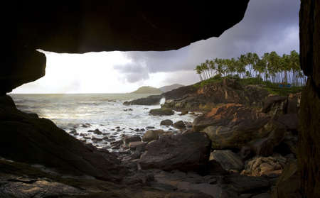 view from a cave at a rocky coastline in south of goa photo