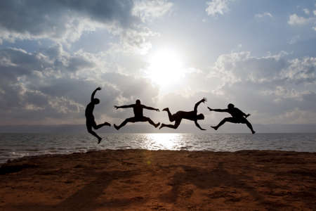 zero gravity: Some guys with Dead-Sea-mud on their skin, are performing a funney jumping scene in front of the dead sea in jordan   Over the sea, some Miles beyond the mountains is Jerusalem