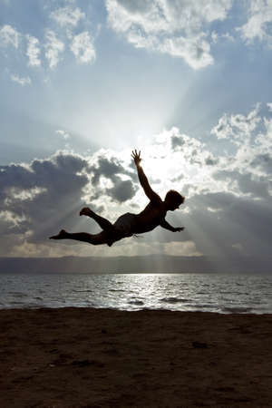 A guy with Dead-Sea-mud on his skin perform jumping scene in front of the dead sea in jordan Stock Photo - 20892945