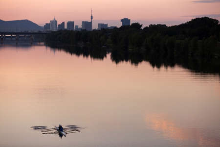 Rowing guys at dusk in the Danube River  Vienna-Austria  with urban skyline of the Danube City  UNO City, Donauturm, Leopoldsberg, etc   in the back