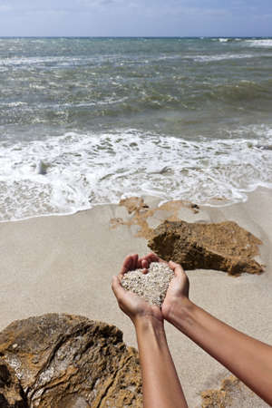 Mellow heart shaping female hands above beach photo
