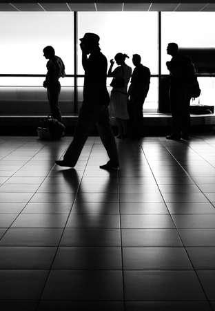 pantomima: siluetas de los pasajeros frente de la cinta transportadora de equipaje esperando en el aeropuerto Foto de archivo