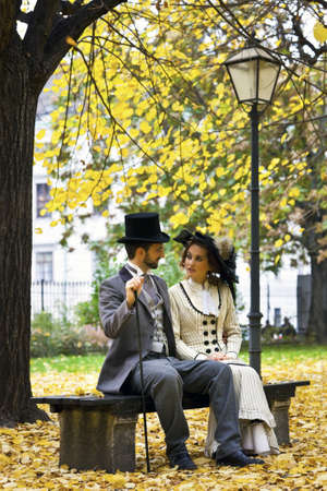 A loving couple, dressed in the style in the end of the 19th century, sitting on a park bench in fall  photo