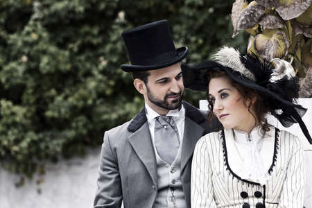A loving couple, dressed in the style in the end of the 19th century, sitting in the park while the woman her longing gaze can wander off into the distance  photo