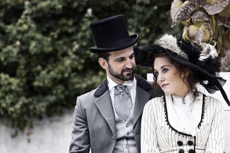 Ein liebendes Paar, das im Stil am Ende des 19. Jahrhunderts gekleidet, sitzen im Park, während die Frau ihre Sehnsucht Blick kann schweifen in die Ferne