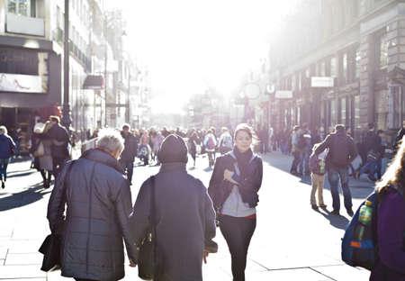 multitud: Muchacha urbana de pie entre la multitud en una calle de la ciudad