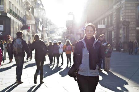 in city: Muchacha urbana de pie entre la multitud en una calle de la ciudad