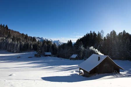 Rural sunny winter landscape with occupied log cabins in the mountains photo