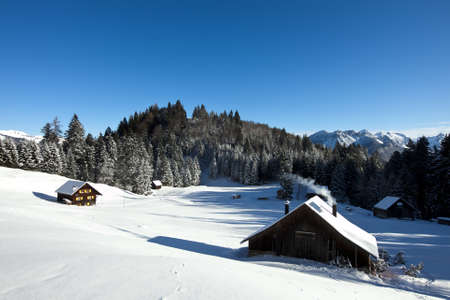 Rural sunny winter landscape with occupied log cabins in the mountains Stock Photo