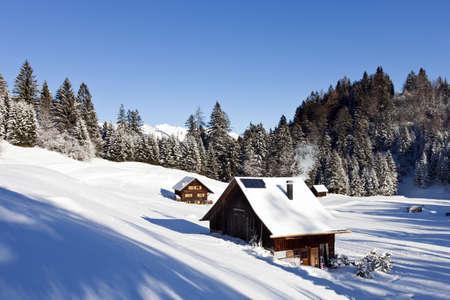 cabaña: Muy detallada foto de un paisaje soleado de invierno con cabañas de madera ocupados y se calienta en las montañas y cimas de montañas cubiertas de nieve en la parte posterior Foto de archivo