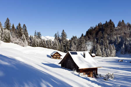log cabin in snow: Very detailed photo of a sunny winter landscape with occupied and heated log cabins in the mountains and snowcovered mountaintops in the back