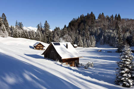 log cabin: Very detailed photo of a sunny winter landscape with occupied and heated log cabins in the mountains and snowcovered mountaintops in the back
